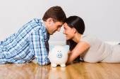 Young couple lying on floor smiling with piggy bank — Stock Photo