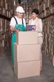 Warehouse worker scanning box with manager — ストック写真