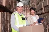 Warehouse worker moving boxes on trolley — Stock Photo