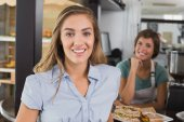 Pretty waitress and customer smiling at camera — Stock Photo