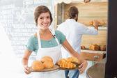 Pretty barista holding trays of baked goods — Stok fotoğraf