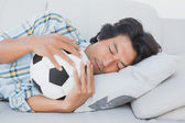 Football fan hugging ball on couch — Photo