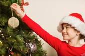Festive little girl hanging a christmas decoration — Foto de Stock