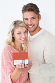Attractive young couple holding mini house — Stock Photo