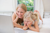 Girl and mother on bed using laptop — Stock fotografie