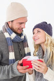 Attractive couple in warm clothing holding gift — Foto de Stock