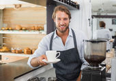 Handsome barista offering a cup of coffee to camera — Stock fotografie