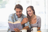 Gelukkige paar genieten van een kopje koffie lezen van een boek — Stockfoto