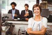 Pretty barista smiling at camera — Stockfoto