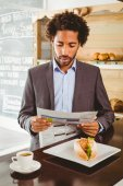 Businessman reading newspaper while having lunch — Stock Photo