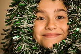 Cute little girl with tinsel around her head — Stock Photo
