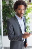 Handsome businessman texting on phone — Stockfoto