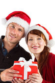 Couple holding a christmas gift — Stockfoto