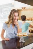 Pretty blonde being tempted by cupcakes — Stock Photo