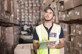 Warehouse worker checking his list — Stockfoto