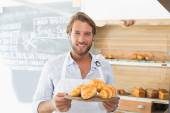 Handsome waiter holding tray of croissants — Stock Photo