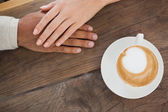 Couple holding hands beside cappuccino — Stock Photo