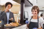 Happy server preparing food at counter — Stock Photo