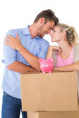 Couple with piggybank over cardboard box — Foto de Stock