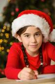Little girl writing letter to santa at christmas — Stock Photo