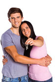 Young couple showing keys to house — Stockfoto