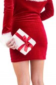Sexy santa girl holding gift behind back — Stock Photo