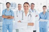 Smiling doctor with fellow doctors — Stock Photo