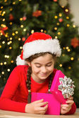 Little girl opening a gift at christmas — Stock Photo
