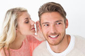Woman whispering secret into a man's ear — Stock Photo