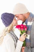 Attractive couple in warm clothing holding flowers — Stok fotoğraf