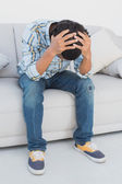 Tensed football fan sitting on couch — Foto Stock