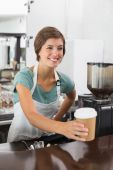 Pretty barista holding disposable cup — Stock Photo