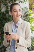 Beautiful businesswoman texting on phone — Stock Photo