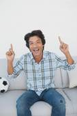 Happy soccer fan cheering while watching tv — Stock Photo