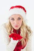 Young woman wearing santa hat as she blows kiss — Foto Stock