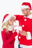 Attractive young couple wearing santa hats with gift — ストック写真