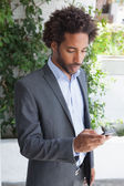 Handsome businessman texting on phone — Stock Photo