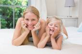 Girl and mother on bed — Stock Photo