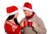 Young festive couple holding mugs — Foto de Stock