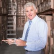 Smiling warehouse manager writing on clipboard — Stock Photo #53920583