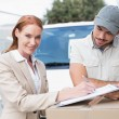 Delivery driver showing where to sign to customer — Stock Photo #53921633