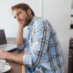 Casual man using laptop having coffee — Stock Photo #53922697