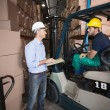 Warehouse manager talking with forklift driver — Stock Photo #53922941