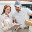 Delivery driver showing where to sign to customer — Stock Photo #53923097