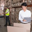 Warehouse manager writing on clipboard — Stock Photo #53924817