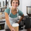 Pretty barista smiling at camera holding disposable cup — Stock Photo #53925545