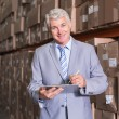 Warehouse manager writing on clipboard — Stock Photo #53925583