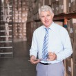 Warehouse manager writing on clipboard — Stock Photo #53925917