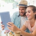 Happy couple enjoying coffee using tablet — Stock Photo #53926073