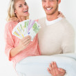 Young man carrying cheerful woman with banknotes — Stock Photo #53926431